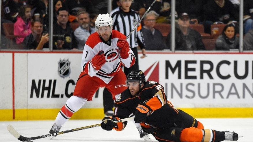 Anaheim Ducks right wing Kyle Palmieri, right, passes the puck under pressure from Carolina Hurricanes defenseman Ryan Murphy during the first period of an NHL hockey game, Tuesday, Feb. 3, 2015, in Anaheim, Calif. (AP Photo/Mark J. Terrill)