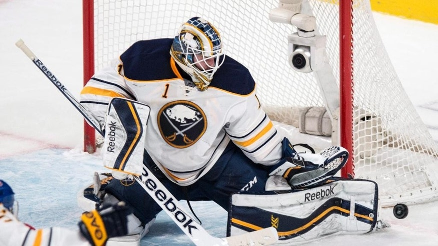 Buffalo Sabres goalie Jhonas Enroth makes a kick save against the Montreal Canadiens during the second period of an NHL hockey game Tuesday, Feb. 3, 2015, in Montreal. (AP Photo/The Canadian Press, Paul Chasson)