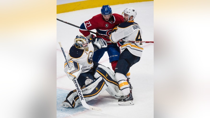 Buffalo Sabres defenseman Josh Gorges pulls Montreal Canadiens' Alex Galchenyuk away from goalie Jhonas Enroth during the third period of an NHL hockey game Tuesday, Feb. 3, 2015, in Montreal. The Sabres won 3-2. (AP Photo/The Canadian Press, Paul Chasson)