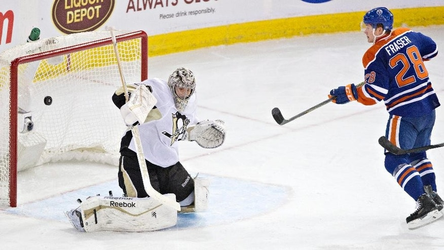 The puck hits the post as Pittsburgh Penguins goalie Marc-Andre Fleury (29) tries to make the save and Edmonton Oilers' Matt Fraser (28) looks for the rebound during the second period on an NHL hockey game, Wednesday, Feb. 4, 2015 in Edmonton, Alberta. (AP Photo/Canadian Press, Jason Franson)