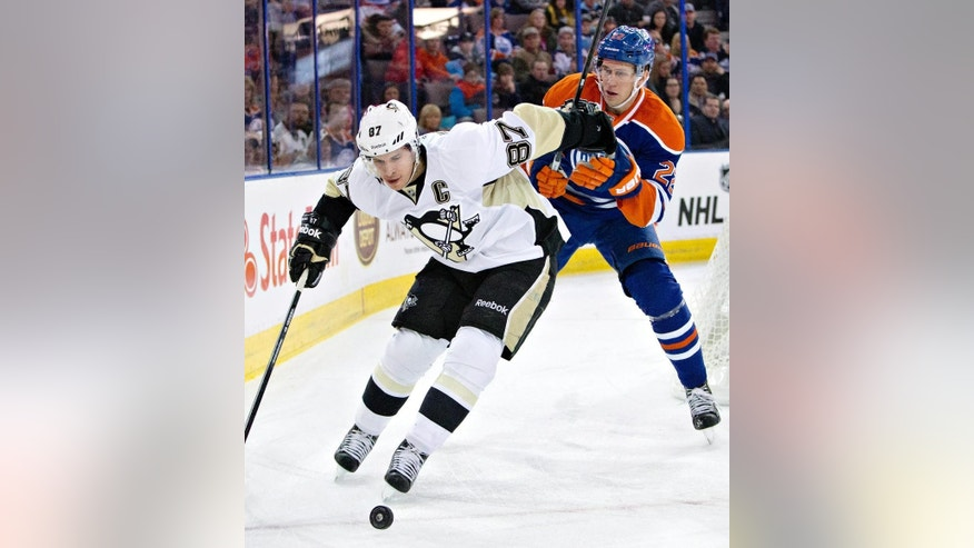 Pittsburgh Penguins' Sidney Crosby (87) controls the puck as Edmonton Oilers' Keith Aulie (22) defends during the first period on an NHL hockey game, Wednesday, Feb. 4, 2015 in Edmonton, Alberta. (AP Photo/Canadian Press, Jason Franson)