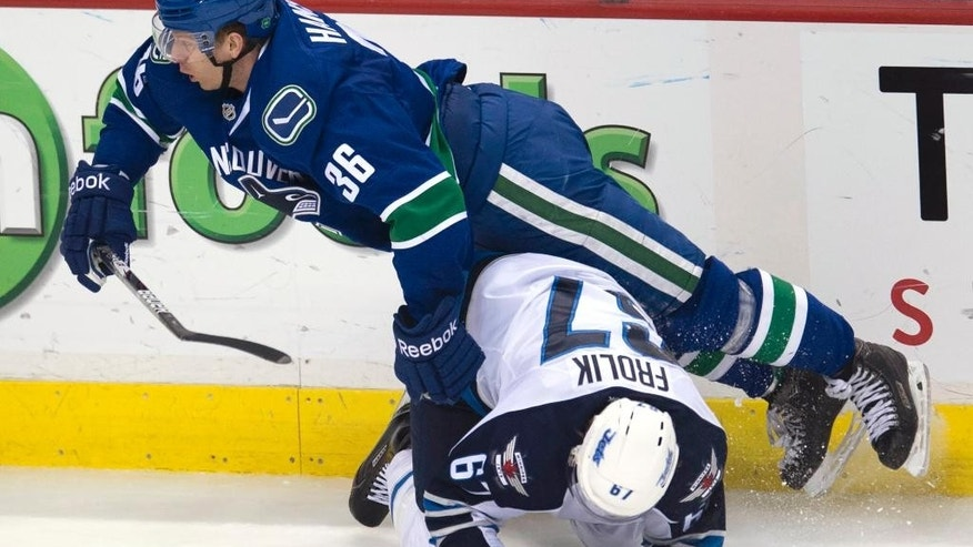 Vancouver Canucks right wing Jannik Hansen (36) trips over Winnipeg Jets right wing Michael Frolik (67) during the third period of an NHL hockey game Tuesday, Feb. 3, 2015, in Vancouver, British Columbia. (AP Photo/The Canadian Press, Jonathan Hayward)