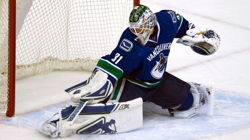 Vancouver Canucks goalie Eddie Lack (31) makes a save during the second period of an NHL game in Vancouver, British Columbia, Tuesday, Feb. 3, 2015. (AP Photo/The Canadian Press, Jonathan Hayward)