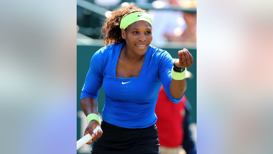 "FILE - In this April 5, 2012, file photoo, Serena Williams gestures after a shot against Marina Erakovic, of New Zealand, during their match at the Family Circle Cup tennis tournament in Charleston, S.C. Williams says she will return to play in the tournament at Indian Wells, California next month after boycotting the event for 14 years. In an exclusive column for time.com, Williams writes about the jeering and booing and an 'undercurrent of racism"" she felt during the 2001 semifinal and final. (AP Photo/Mic Smith, File)"