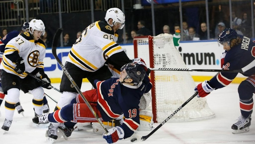 Boston Bruins defenseman Kevan Miller (86) levels New York Rangers right wing Jesper Fast (19) of Sweden as New York Rangers left wing Carl Hagelin (62) of Sweden maneuvers the puck in front of the crease in the second period of an NHL hockey game at Madison Square Garden in New York, Wednesday, Feb. 4, 2015. (AP Photo/Kathy Willens)