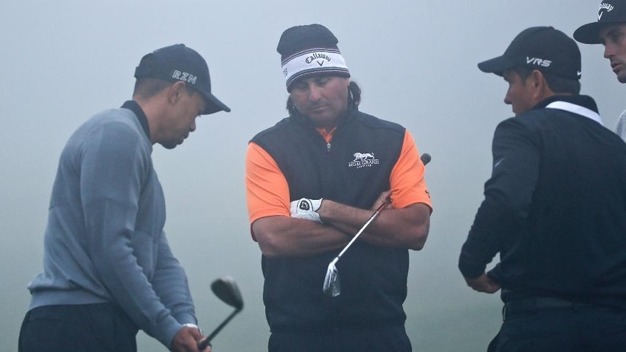 Tiger Woods works on his short game technique as fellow PGA tour player Pat Perez, center, and coach Chris Como look on during a fog delay prior to the pro-am at the Framers Insurance Open golf tournament at Torrey Pines, Wednesday, Feb. 4, 2015, in San Diego. (AP Photo/Lenny Ignelzi)