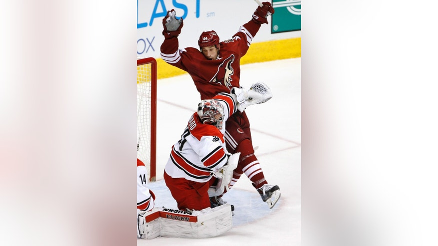 Carolina Hurricanes' Cam Ward gives Arizona Coyotes' B.J. Crombeen, rear, a shove during the first period of an NHL hockey game Thursday, Feb. 5, 2015, in Glendale, Ariz. (AP Photo/Ross D. Franklin)