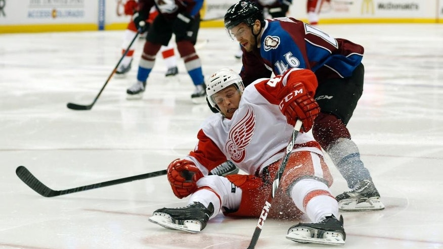 Detroit Red Wings center Luke Glendening, front, reaches out to control the puck as he loses his footing while driving for a shot past Colorado Avalanche defenseman Stefan Elliott in the second period of an NHL hockey game Thursday, Feb. 5, 2015, in Denver. (AP Photo/David Zalubowski)