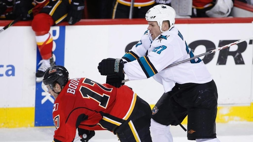 Calgary Flames' Lance Bouma, left, takes a hit from San Jose Sharks' Scott Hannan during the second period of an NHL hockey game Wednesday, Feb. 4, 2015, in Calgary, Alberta. (AP Photo/The Canadian Press, Larry MacDougal)