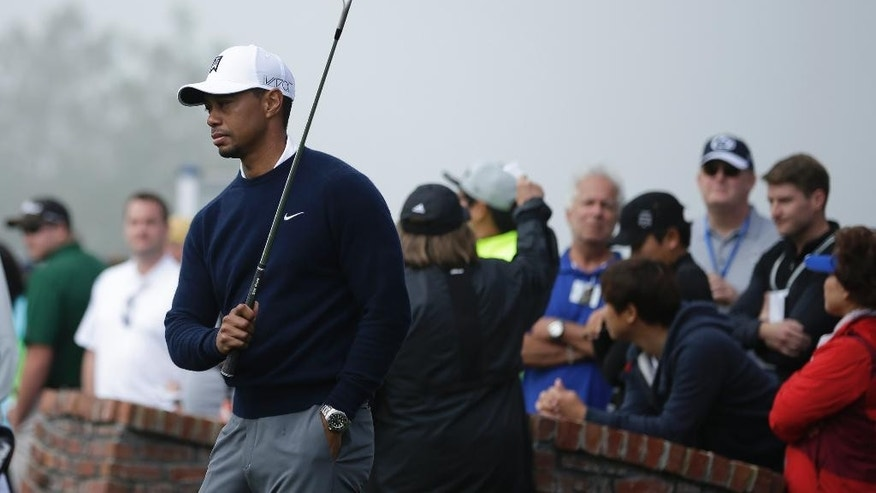 Tiger Woods takes a few one-arm swings during a fog delay while waiting to tee off during the first round of the Farmers Insurance Open golf tournament Thursday, Feb. 5, 2015, in San Diego. (AP Photo/Gregory Bull)