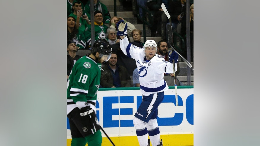 Tampa Bay Lightning center Steven Stamkos (91) celebrates scoring a goal as Dallas Stars right wing Patrick Eaves (18) skates past during the first period of an NHL hockey game Thursday, Feb. 5, 2015, in Dallas. (AP Photo/LM Otero)