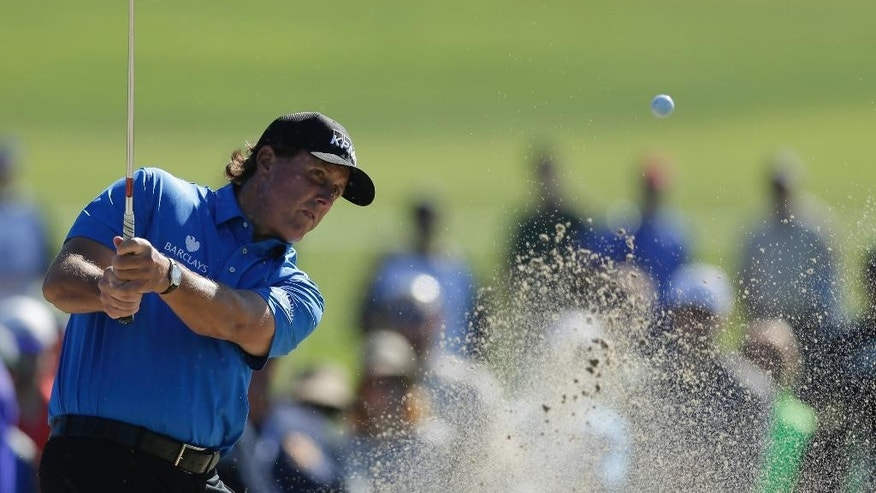 Phil Mickelson hits out of a bunker on the 11th hole of the North Course at Torrey Pines during the second round of the Farmers Insurance Open golf tournament Friday, Feb. 6, 2015, in San Diego. (AP Photo/Gregory Bull)