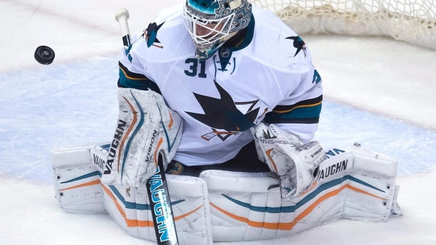 San Jose Sharks goalie Antti Niemi (31) keeps his eye on the puck during the second period of an NHL hockey game against the Vancouver Canucks on Thursday, Feb. 5, 2015, in Vancouver, British Columbia. (AP Photo/The Canadian Press, Jonathan Hayward)