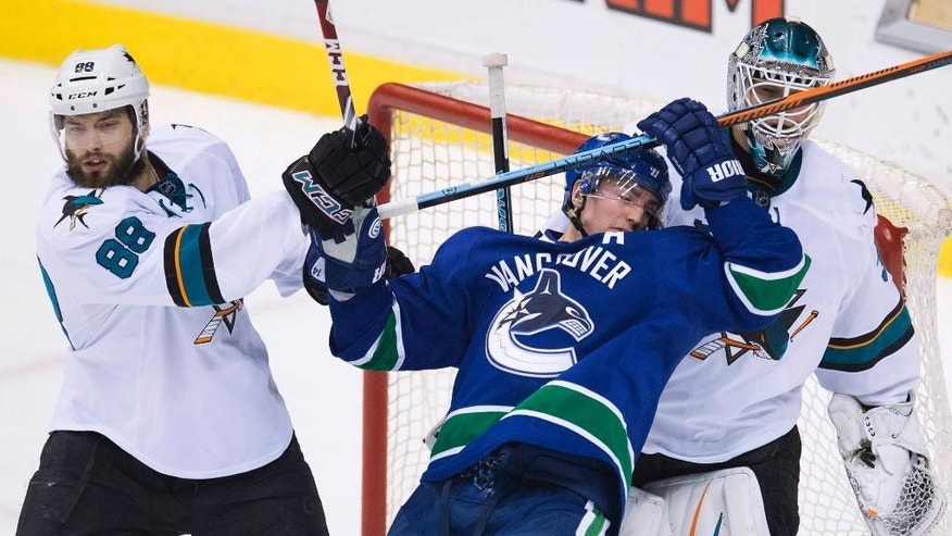 San Jose Sharks defenseman Brent Burns (88) clears Vancouver Canucks left wing Alex Burrows (14) from in front of Sharks goalie Antti Niemi (31) during the second period of an NHL hockey game Thursday, Feb. 5, 2015, in Vancouver, British Columbia. (AP Photo/The Canadian Press, Jonathan Hayward)