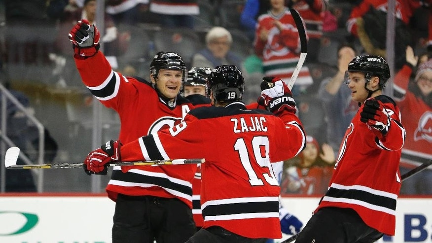 New Jersey Devils left wing Patrik Elias, left, of the Czech Republic, celebrates with teammates after scoring a goal against the Toronto Maple Leafs during the second period of an NHL hockey game, Friday, Feb. 6, 2015, in Newark, N.J. The score gives Elias 400th career goal. (AP Photo/Julio Cortez)
