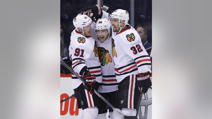 Chicago Blackhawks' Patrick Kane (88) celebrates his goal against the Winnipeg Jets with Brad Richards, left, and Michal Rozsival (32) during the second period of an NHL hockey game Friday, Feb. 6, 2015, in Winnipeg, Manitoba. (AP Photo/The Canadian Press, John Woods)