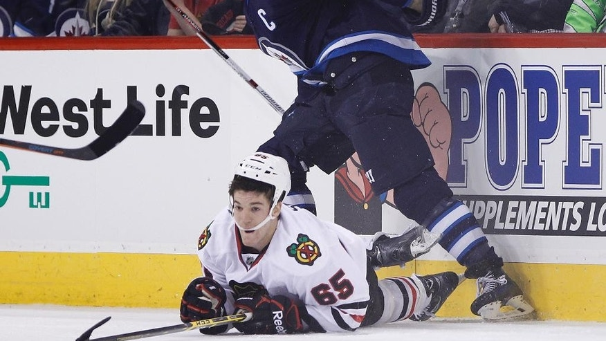 Winnipeg Jets' Andrew Ladd (16) dumps Chicago Blackhawks' Andrew Shaw (65) to the ice during the second period of an NHL hockey game Friday, Feb. 6, 2015, in Winnipeg, Manitoba. (AP Photo/The Canadian Press, John Woods)