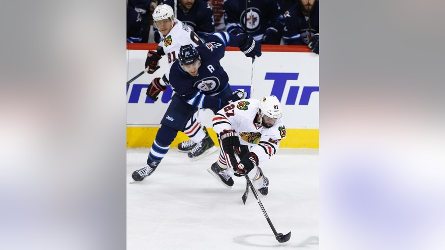 Chicago Blackhawks' Johnny Oduya (27) plays the puck as he is hauled down by Winnipeg Jets' Blake Wheeler (26) during the first period of an NHL hockey game Friday, Feb. 6, 2015, in Winnipeg, Manitoba. (AP Photo/The Canadian Press, John Woods)