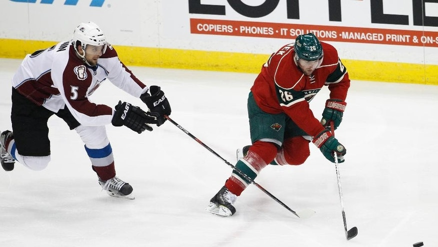 Minnesota Wild left wing Thomas Vanek (26), of Austria, and Colorado Avalanche defenseman Nate Guenin (5) chase the puck during the first period of an NHL hockey game in St. Paul, Minn., Saturday, Feb. 7, 2015. (AP Photo/Ann Heisenfelt)