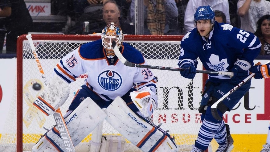 Toronto Maple Leafs centre Mike Santorelli (25) and Edmonton Oilers goaltender Viktor Fasth keep an eye on the puck during the first period of an NHL hockey game Saturday, Feb. 7, 2015, in Toronto. (AP Photo/The Canadian Press, Frank Gunn)