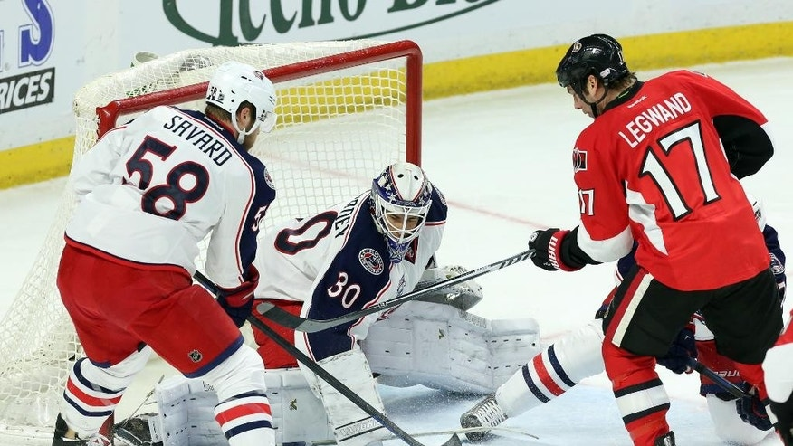 Columbus Blue Jackets goaltender Curtis McElhinney (30) pushes the puck away as teammate David Savard (58) and Ottawa Senators' David Legwand (17) look on during the first period on an NHL hockey game, Saturday, Feb. 7, 2015 in Ottawa, Ontario.  (AP Photo/Canadian Press, Fred Chartrand)