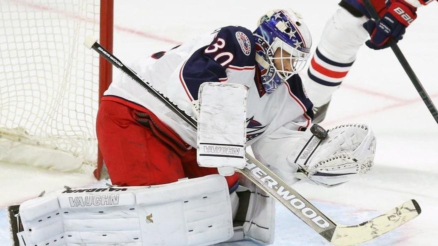 Columbus Blue Jackets goaltender Curtis McElhinney (30) makes a glove save against the Ottawa Senators during the first period on an NHL hockey game, Saturday, Feb. 7, 2015 in Ottawa, Ontario.  (AP Photo/Canadian Press, Fred Chartrand)