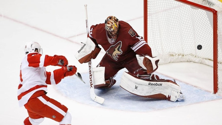 Detroit Red Wings' Tomas Tatar (21), of the Czech Republic, scores against Arizona Coyotes' Mike Smith, right, during the third period of an NHL hockey game Saturday, Feb. 7, 2015, in Glendale, Ariz.  The Red Wings defeated the Coyotes 3-1. (AP Photo/Ross D. Franklin)