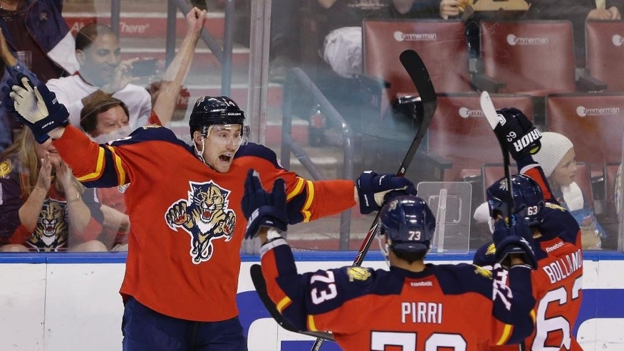 Florida Panthers left wing Tomas Fleischmann, left, of the Czech Republic, celebrates with teammates center Brandon Pirri (73) and center Dave Bolland (63) after scoring a goal during the second period of an NHL hockey game against the Nashville Predators, Sunday, Feb. 8, 2015, in Sunrise, Fla. (AP Photo/Wilfredo Lee)