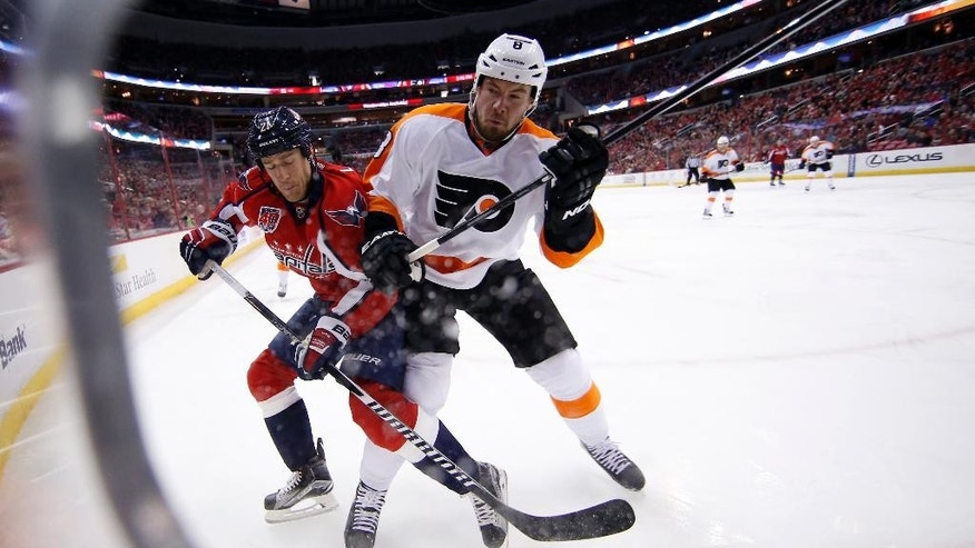 Washington Capitals center Brooks Laich (21) is checked by Philadelphia Flyers defenseman Nicklas Grossmann (8), from Sweden, after Laich passed the puck in the first period of an NHL hockey game Sunday, Feb. 8, 2015, in Washington. (AP Photo/Alex Brandon)