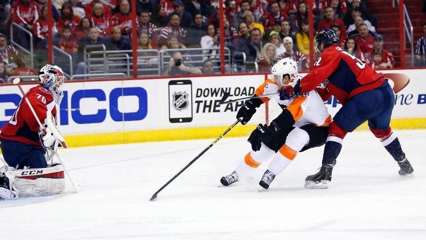 Philadelphia Flyers center Chris VandeVelde (76) chases the puck with Washington Capitals defenseman Mike Green (52) behind him, and goalie Braden Holtby (70) in the goal, in the second period of an NHL hockey game Sunday, Feb. 8, 2015, in Washington. (AP Photo/Alex Brandon)