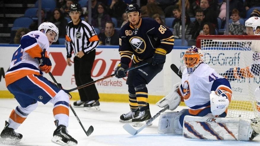 New York Islanders defenseman Thomas Hickey (14) turns to face an incoming shot while Buffalo Sabres right winger Chris Stewart (80) and Islander goaltender Jaroslav Halak (41), of Slovakia, look on  during the first period of an NHL hockey game Sunday, Feb. 8, 2015, in Buffalo, N.Y. (AP Photo/Gary Wiepert)