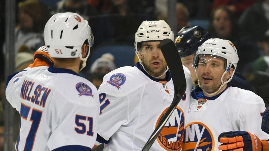 New York Islanders' Frans Nielsen (51), John Tavares (91), and Anders Lee (27) celebrate a goal by Lee during the second period of an NHL hockey game against the Buffalo Sabres, Sunday, Feb. 8, 2015, in Buffalo, N.Y. (AP Photo/Gary Wiepert)