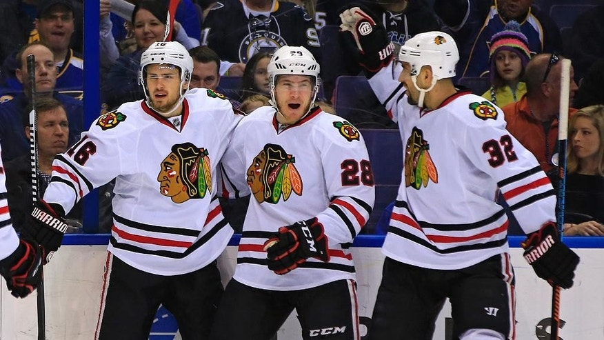 Chicago Blackhawks' Marcus Kruger, left, of Sweden, is congratulated by teammates Ben Smith, center, and Michal Rozsival, right, of the Czech Republic, after scoring a goal during the first period of an NHL hockey game against the St. Louis Blues, Sunday, Feb. 8, 2015, in St. Louis. (AP Photo/Billy Hurst)