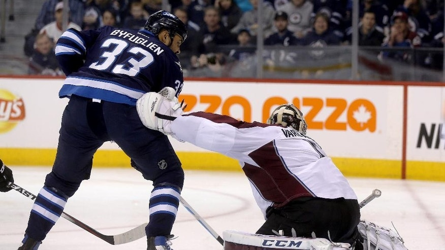 Winnipeg Jets' Dustin Byfuglien (33) scores on Colorado Avalanche goaltender Semyon Varlamov (1) during second period NHL hockey action in Winnipeg, Manitoba, Sunday, Feb. 8, 2015.  (AP Photo/The Canadian Press, Trevor Hagan)