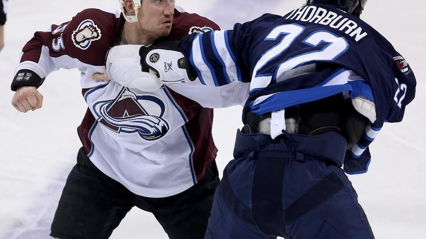 Colorado Avalanche's Cody McLeod (55) fights with Winnipeg Jets' Chris Thorburn (22) during the first period of an NHL hockey game in Winnipeg, Manitoba, Sunday, Feb. 8, 2015. (AP Photo/The Canadian Press, Trevor Hagan)