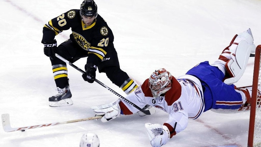 Boston Bruins left wing Daniel Paille (20) and Montreal Canadiens goalie Carey Price (31), vie for control of the puck during the first period of an NHL hockey game, Sunday, Feb. 8, 2015, in Boston. (AP Photo/Steven Senne)