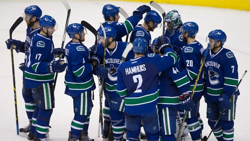 Vancouver Canucks goalie Ryan Miller, third dein right, is congratulated by teammates on his shutout against the Pittsburgh Penguins in an NHL hockey game in Vancouver, British Columbia, on Saturday, Feb. 7, 2015. Vancouver won 5-0. (AP Photo/The Canadian Press, Darryl Dyck)