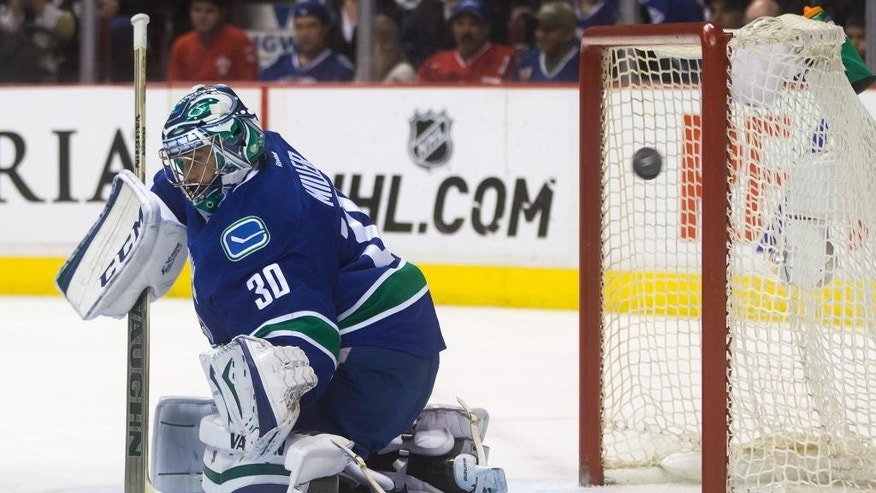 Vancouver Canucks goalie Ryan Miller deflects a Pittsburgh Penguins shot wide of the net during the first period of an NHL hockey game in Vancouver, British Columbia, on Saturday, Feb. 7, 2015. (AP Photo/The Canadian Press, Darryl Dyck)