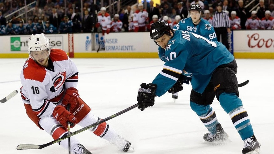 Carolina Hurricanes' Elias Lindholm (16) is defended by San Jose Sharks' Andrew Desjardins during the second period of an NHL hockey game Saturday, Feb. 7, 2015, in San Jose, Calif. (AP Photo/Marcio Jose Sanchez)