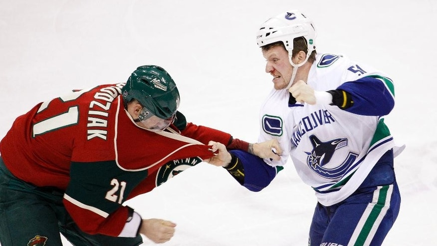 Vancouver Canucks right wing Derek Dorsett, right, and Minnesota Wild center Kyle Brodziak (21) fight during the first period of an NHL hockey game in St. Paul, Minn., Monday, Feb. 9, 2015. (AP Photo/Ann Heisenfelt)