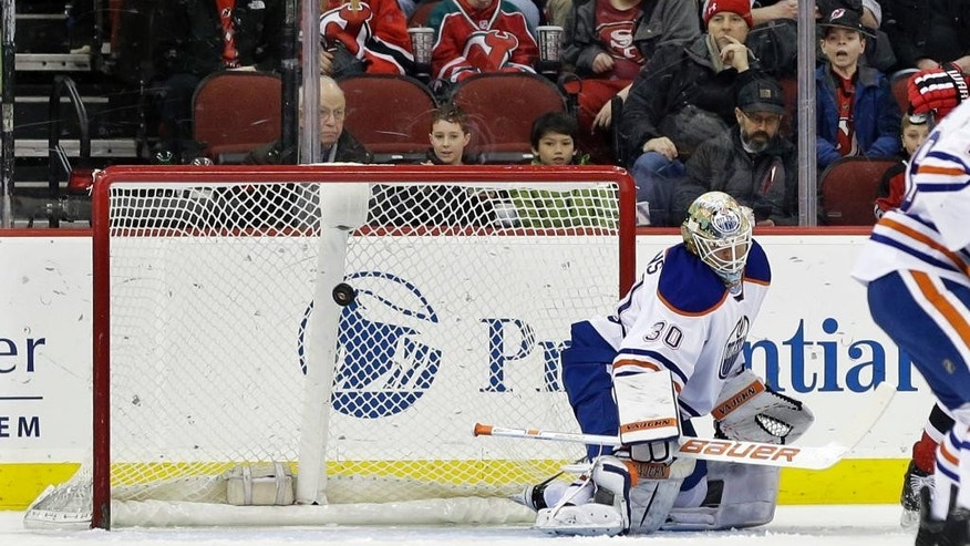 Edmonton Oilers goaltender Viktor Fasth is unable to stop a shot by New Jersey Devils left wing Patrik Elias, of the Czech Republic, during the first period of an NHL hockey game Monday, Feb. 9, 2015, in Newark, N.J. (AP Photo/Mel Evans)