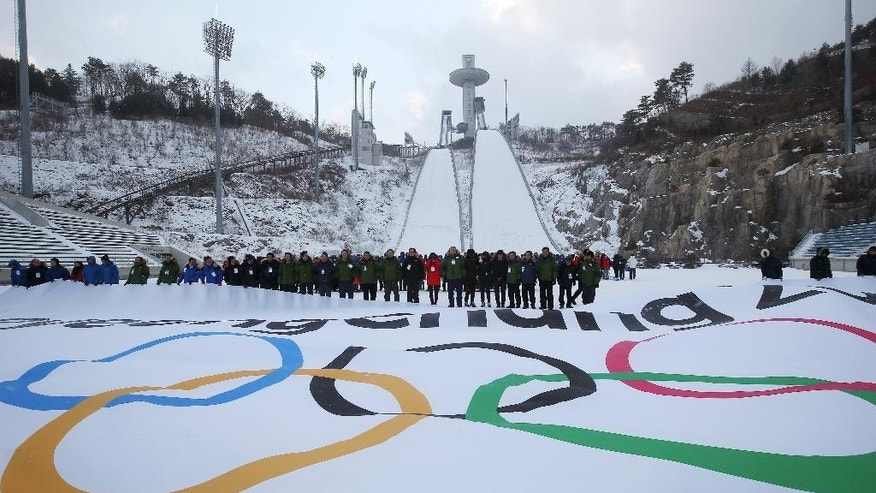 """Participants attend an event marking the three-year countdown to the start of the 2018 Winter Olympics at Alpensia Ski Jumping Center in Pyeongchang, South Korea, Monday, Feb. 9, 2015. The organizing committee celebrated Monday's milestone with an event at Pyeongchang's ski jumping center and Olympic stadium site. Kim Jong, an official with South Korea's sports ministry, said officials are """"at a critical point"""" in preparations for the games, which will run from Feb. 9-25, 2018. (AP Photo/Yonhap, Han Jong-chan)  KOREA OUT"""