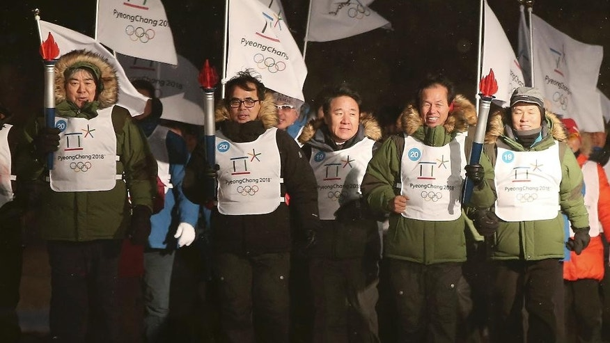Pyeongchang 2018 Winter Olympics Organizing Committee President Cho-Yang-ho, left, South Korea's Culture, Sports and Tourism Vice Minister Kim Jong, second left, and Gangwon Province Gov. Choi Moon-soon, second right, run with mock Olympic torches during an event marking the three-year countdown to the start of the 2018 Winter Olympics in Pyeongchang, South Korea, Monday, Feb. 9, 2015. The South Korean government recently rejected a proposal by the International Olympic Committee to halt construction on a new bobsled, luge and skeleton venue and relocate the events to an existing sliding center in another country. The IOC said the move would have saved $120 million in construction costs and $3.5 million in yearly maintenance fees. (AP Photo/Yonhap, Han Jong-chan)  KOREA OUT