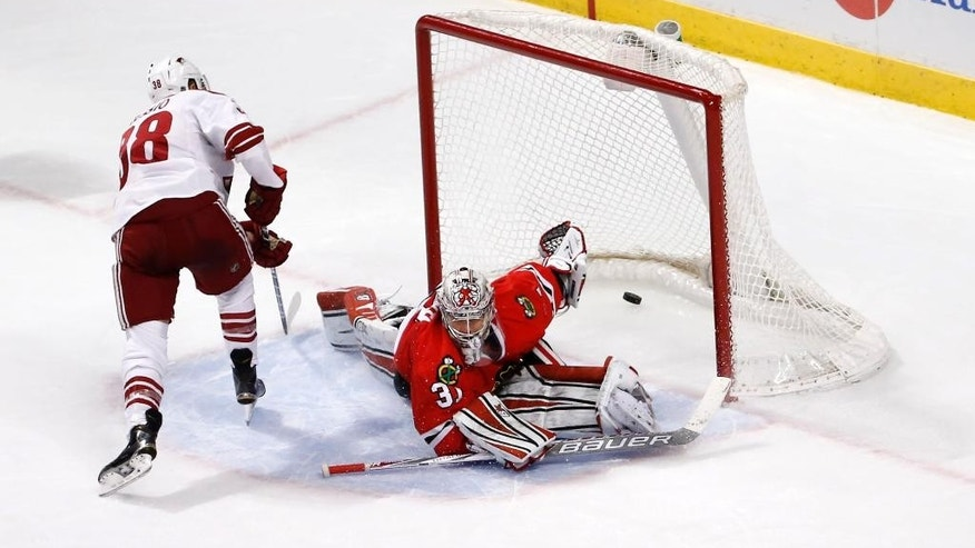Arizona Coyotes left wing Lucas Lessio (38) scores on Chicago Blackhawks goalie Antti Raanta during a shootout period of an NHL hockey game Monday, Feb. 9, 2015, in Chicago. The Coyotes won 3-2. (AP Photo/Charles Rex Arbogast)