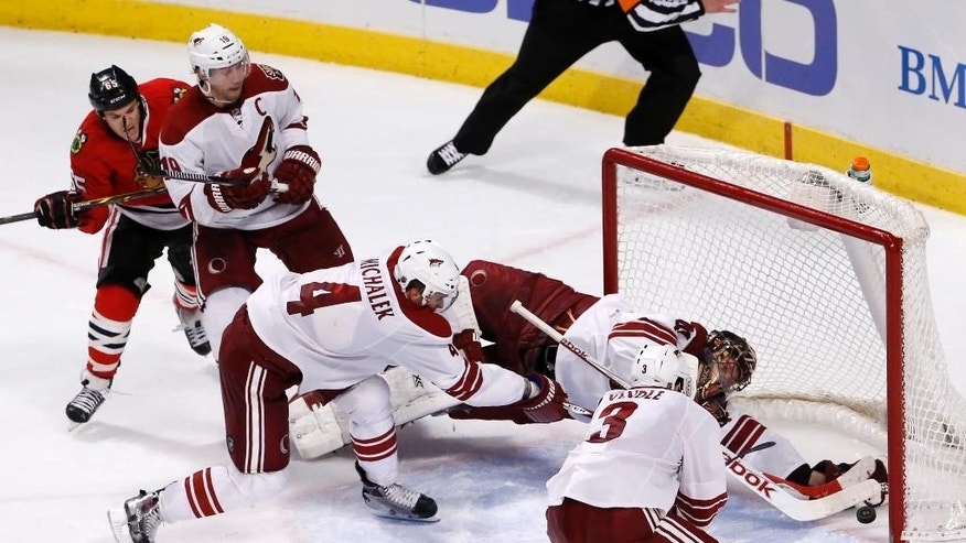 Arizona Coyotes goalie Mike Smith (41) makes a save on a shot by Chicago Blackhawks center Andrew Shaw, left, before the complete puck crossed the goal line as Shane Doan (19), Zbynek Michalek (4), and Keith Yandle also defend during an overtime period of an NHL hockey game Monday, Feb. 9, 2015, in Chicago. The play was reviewed and confirmed a no goal as the Coyotes went on and won in a shootout period 3-2. (AP Photo/Charles Rex Arbogast)