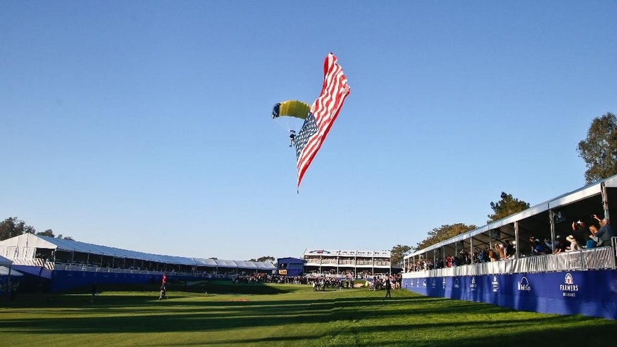 A sky diver lands on the 18th hole of the south course at Torrey Pines where he delivered the winner's trophy for the  Farmers Insurance Open golf tournament Sunday, Feb. 8, 2015, in San Diego. (AP Photo/Lenny Ignelzi)