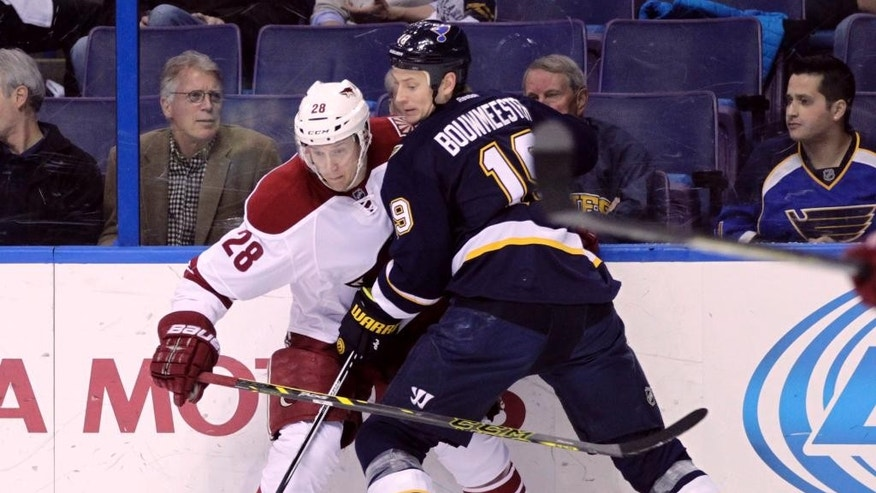 St. Louis Blues' Jay Bouwmeester (19) battles Arizona Coyotes' Lauri Korpikoski (28) for the lose puck in the first period of an NHL hockey game, Tuesday, Feb. 10, 2015, in St. Louis. (AP Photo/Tom Gannam)