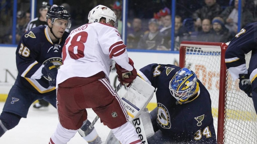 St. Louis Blues goalie Jake Allen (34) makes a save on a shot from Arizona Coyotes' Lucas Lessio (38), as St. Louis Blues' Paul Stastny (26) defends, in the first period of an NHL hockey game, Tuesday, Feb. 10, 2015, in St. Louis. (AP Photo/Tom Gannam)