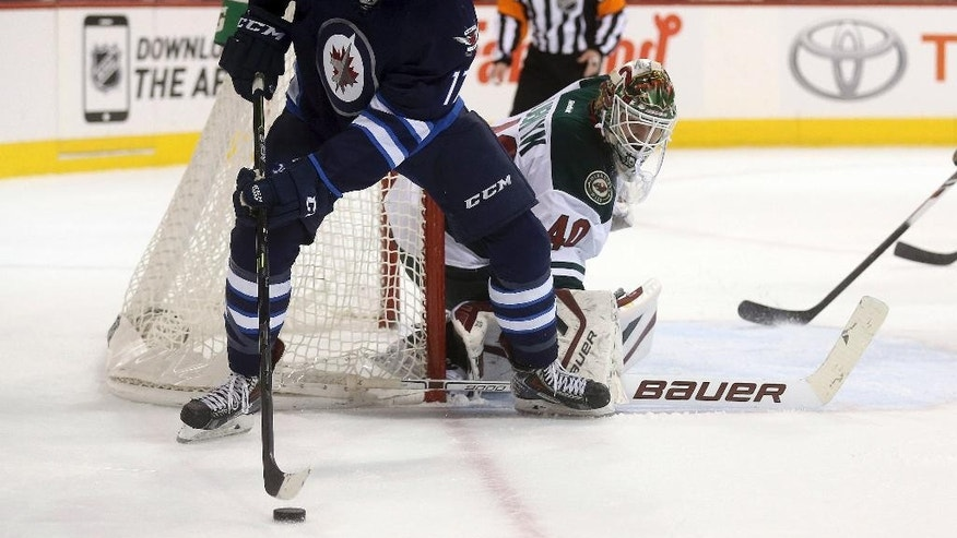 Winnipeg Jets' Adam Lowry (17) carries the puck near Minnesota Wild goaltender Devan Dubnyk (40) during the second period of an NHL hockey game Tuesday, Feb. 10, 2015, in Winnipeg, Manitoba. (AP Photo/The Canadian Press, Trevor Hagan)
