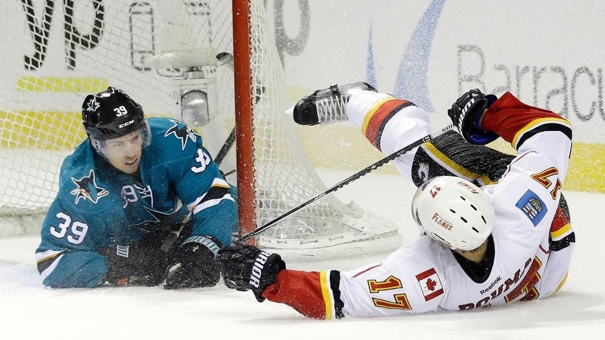 Calgary Flames' Lance Bouma (17) falls after colliding with San Jose Sharks' Logan Couture (39) during the second period of an NHL hockey game Monday, Feb. 9, 2015, in San Jose, Calif. (AP Photo/Marcio Jose Sanchez)